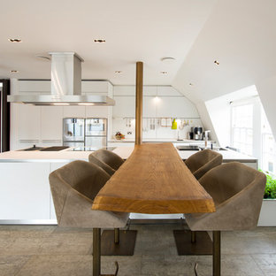 Large contemporary galley kitchen/diner in Hampshire with flat-panel cabinets, white cabinets, wood worktops, white splashback, stainless steel appliances, multiple islands, grey floors and brown worktops.