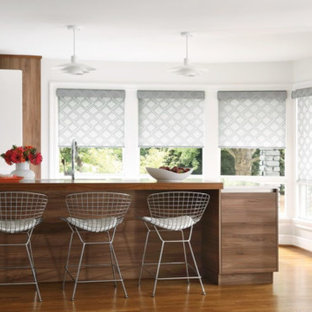 Mid-sized contemporary enclosed kitchen designs - Inspiration for a mid-sized contemporary l-shaped medium tone wood floor and brown floor enclosed kitchen remodel in San Diego with an undermount sink, flat-panel cabinets, white cabinets, solid surface countertops, white appliances, an island and white countertops