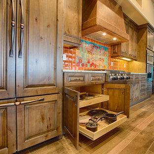 Пример оригинального дизайна: большая прямая кухня в стиле фьюжн с обеденным столом, фасадами с выступающей филенкой, фасадами цвета дерева среднего тона, гранитной столешницей, оранжевым фартуком, фартуком из керамической плитки и техникой из нержавеющей стали
