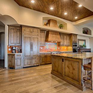 フェニックスの広いサンタフェスタイルのおしゃれなキッチン (アンダーカウンターシンク、レイズドパネル扉のキャビネット、中間色木目調キャビネット、木材カウンター、オレンジのキッチンパネル、セラミックタイルのキッチンパネル、シルバーの調理設備、無垢フローリング) の写真
