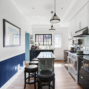 Transitional kitchen photos - Example of a transitional single-wall medium tone wood floor kitchen design in New York with flat-panel cabinets, white cabinets, white appliances, an island and glass tile backsplash