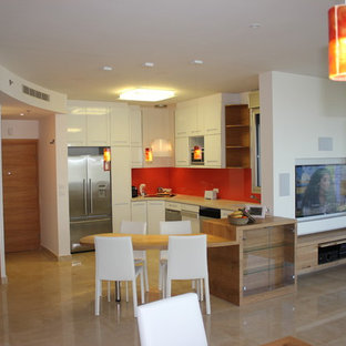 Mid-sized modern l-shaped eat-in kitchen in Tel Aviv with a single-bowl sink, glass-front cabinets, white cabinets, soapstone benchtops, orange splashback, glass sheet splashback, stainless steel appliances, marble floors, with island and beige floor.