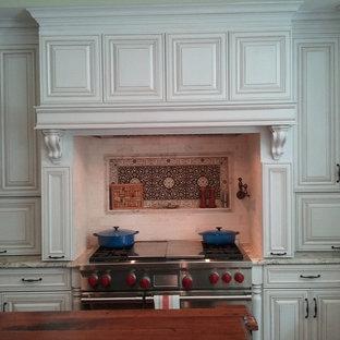 Elegant u-shaped eat-in kitchen photo in Other with a farmhouse sink, raised-panel cabinets, beige cabinets, wood countertops, beige backsplash and stone tile backsplash