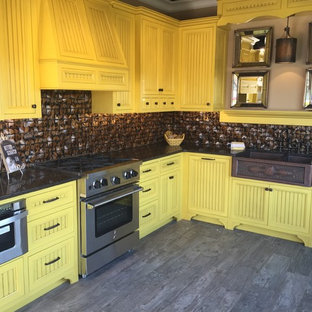 Photo of a large country l-shaped eat-in kitchen in Portland with a farmhouse sink, beaded inset cabinets, yellow cabinets, granite benchtops, brown splashback, ceramic splashback, stainless steel appliances, porcelain floors and no island.