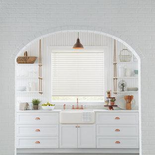 ニューヨークの大きいカントリー風おしゃれなキッチン (エプロンフロントシンク、シェーカースタイル扉のキャビネット、白いキャビネット、大理石カウンター、グレーの床、白いキッチンパネル、木材のキッチンパネル、セメントタイルの床、アイランドなし、白いキッチンカウンター) の写真