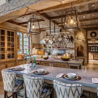 Rustic kitchen inspiration - Example of a mountain style limestone floor kitchen design in New York with a farmhouse sink, recessed-panel cabinets, concrete countertops, gray backsplash, ceramic backsplash, stainless steel appliances and an island