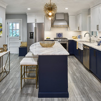 Eat-in kitchen - mid-sized transitional l-shaped porcelain tile and gray floor eat-in kitchen idea in Charlotte with a farmhouse sink, recessed-panel cabinets, blue cabinets, marble countertops, white backsplash, mosaic tile backsplash, stainless steel appliances, an island and white countertops