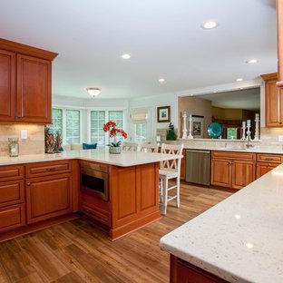 オレンジカウンティの広いトラディショナルスタイルのおしゃれなキッチン (ダブルシンク、レイズドパネル扉のキャビネット、中間色木目調キャビネット、珪岩カウンター、ベージュキッチンパネル、セラミックタイルのキッチンパネル、シルバーの調理設備、無垢フローリング) の写真