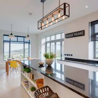 Photo of a large contemporary u-shaped eat-in kitchen in Devon with a farmhouse sink, flat-panel cabinets, white cabinets, granite benchtops, black splashback, stone slab splashback, black appliances, limestone floors, with island and beige floor.