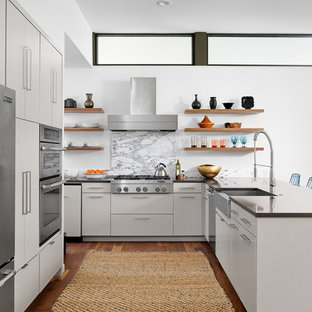 Inspiration for a midcentury u-shaped eat-in kitchen in Austin with a farmhouse sink, flat-panel cabinets, grey cabinets, quartzite benchtops, stone slab splashback, stainless steel appliances, medium hardwood floors and a peninsula.