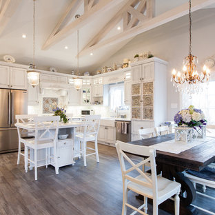 Design ideas for a mid-sized traditional l-shaped eat-in kitchen in Other with a farmhouse sink, raised-panel cabinets, distressed cabinets, white splashback, subway tile splashback, stainless steel appliances, light hardwood floors, with island and brown floor.