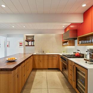 Пример оригинального дизайна: п-образная кухня в стиле ретро с врезной раковиной, плоскими фасадами, оранжевыми фасадами, столешницей из кварцевого агломерата, техникой из нержавеющей стали, бетонным полом и полуостровом