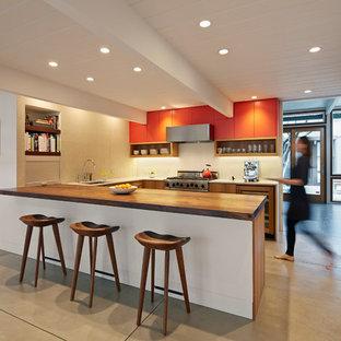 Foto på ett retro u-kök, med släta luckor, orange skåp, träbänkskiva, rostfria vitvaror och betonggolv