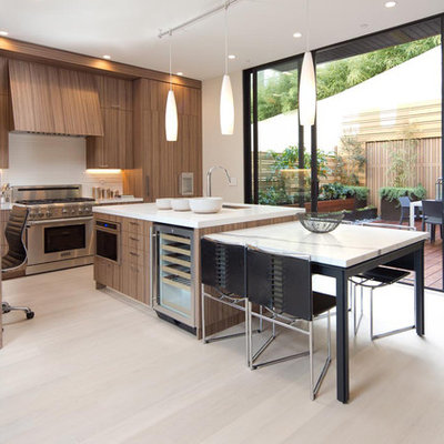 Mid-sized trendy l-shaped light wood floor eat-in kitchen photo in San Francisco with an undermount sink, flat-panel cabinets, medium tone wood cabinets, white backsplash, paneled appliances and an island