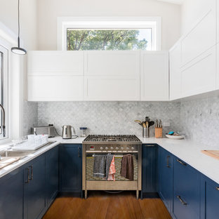Design ideas for a transitional u-shaped kitchen in Sydney with a double-bowl sink, shaker cabinets, blue cabinets, white splashback, mosaic tile splashback, stainless steel appliances, medium hardwood floors, no island, brown floor and white benchtop.