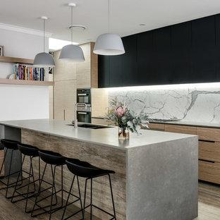 Diseño de cocina de galera, contemporánea, de tamaño medio, con fregadero de doble seno, armarios con paneles lisos, puertas de armario negras, salpicadero metalizado, salpicadero de mármol, electrodomésticos negros, una isla y suelo marrón