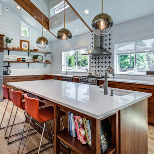 This is an example of a midcentury l-shaped kitchen in Seattle with an undermount sink, flat-panel cabinets, dark wood cabinets, multi-coloured splashback, stainless steel appliances, light hardwood floors, with island and white benchtop.