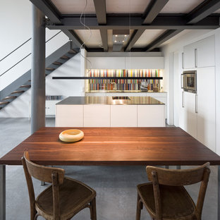 Design ideas for a mid-sized industrial open plan kitchen in Munich with an integrated sink, flat-panel cabinets, white cabinets, stainless steel benchtops, multi-coloured splashback, stainless steel appliances and with island.