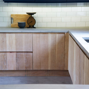 Inspiration for an industrial u-shaped open plan kitchen in Other with a double-bowl sink, flat-panel cabinets, light wood cabinets, concrete benchtops, white splashback, ceramic splashback, stainless steel appliances, concrete floors and a peninsula.