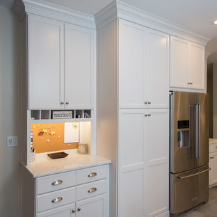 Inspiration for a mid-sized beach style u-shaped kitchen in Boston with a farmhouse sink, recessed-panel cabinets, white cabinets, quartz benchtops, grey splashback, stone tile splashback, stainless steel appliances, ceramic floors, a peninsula and grey floor.