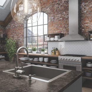 Inspiration for a large industrial u-shaped open plan kitchen in Atlanta with a drop-in sink, open cabinets, dark wood cabinets, laminate benchtops, white splashback, subway tile splashback, stainless steel appliances, light hardwood floors and with island.