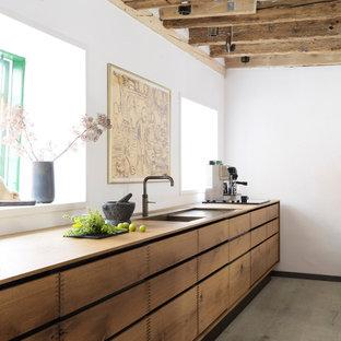 コペンハーゲンの広いラスティックスタイルのおしゃれなキッチン (フラットパネル扉のキャビネット、中間色木目調キャビネット、ドロップインシンク、木材カウンター、塗装フローリング) の写真