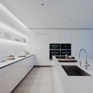 Ejemplo de cocina comedor en L, moderna, de tamaño medio, con fregadero de un seno, armarios con paneles lisos, puertas de armario blancas, salpicadero blanco, suelo de madera clara, una isla, encimera de mármol, electrodomésticos blancos y encimeras grises