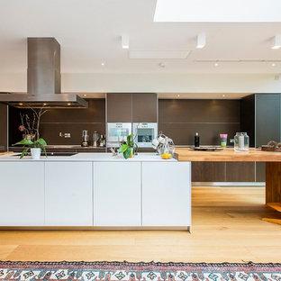 Diseño de cocina de galera, moderna, con armarios con paneles lisos, puertas de armario de madera en tonos medios, salpicadero marrón, electrodomésticos con paneles, suelo de madera clara y una isla