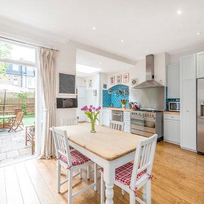 Elegant medium tone wood floor eat-in kitchen photo in London with shaker cabinets, white cabinets, wood countertops, blue backsplash, subway tile backsplash and stainless steel appliances