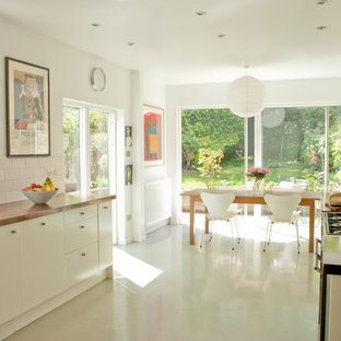 Eat-in kitchen - contemporary white floor eat-in kitchen idea in Other with subway tile backsplash, an undermount sink, flat-panel cabinets, white cabinets, wood countertops and white backsplash