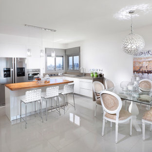 Contemporary eat-in kitchen ideas - Example of a trendy l-shaped eat-in kitchen design in Other with stainless steel appliances, wood countertops, flat-panel cabinets and white cabinets