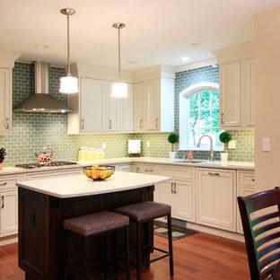 Kleine Klassische Wohnküche in L-Form mit Einbauwaschbecken, Kassettenfronten, weißen Schränken, Küchenrückwand in Grün, Rückwand aus Keramikfliesen, braunem Holzboden, Kücheninsel, braunem Boden und weißer Arbeitsplatte in New York