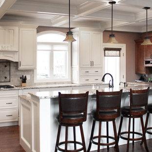 Mittelgroße Klassische Wohnküche in L-Form mit Einbauwaschbecken, profilierten Schrankfronten, weißen Schränken, Granit-Arbeitsplatte, Küchenrückwand in Beige, Rückwand aus Travertin, Küchengeräten aus Edelstahl, dunklem Holzboden, Kücheninsel, braunem Boden und bunter Arbeitsplatte in New York