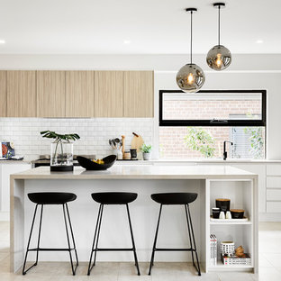 This is an example of a modern l-shaped kitchen in Melbourne with an undermount sink, flat-panel cabinets, light wood cabinets, white splashback, subway tile splashback, stainless steel appliances, with island, beige floor and beige benchtop.
