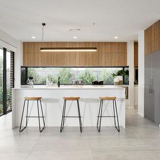Foto på ett funkis kök, med släta luckor, skåp i mellenmörkt trä, fönster som stänkskydd, rostfria vitvaror, en köksö och grått golv
