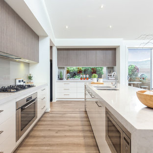 This is an example of a contemporary galley open plan kitchen in Adelaide with a double-bowl sink, flat-panel cabinets, white cabinets, marble benchtops, grey splashback, glass sheet splashback, stainless steel appliances, light hardwood floors and an island.
