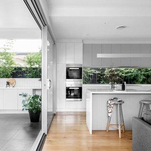 Diseño de cocina de galera, contemporánea, abierta, con fregadero bajoencimera, armarios con paneles lisos, puertas de armario de madera oscura, salpicadero de vidrio, electrodomésticos negros, suelo de madera en tonos medios, una isla y suelo beige