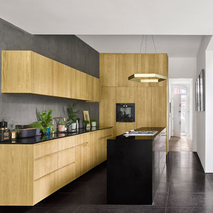 Inspiration for a contemporary l-shaped kitchen in London with an integrated sink, flat-panel cabinets, light wood cabinets, grey splashback, an island, black floors and black worktops.