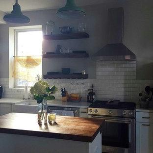 Réalisation d'une petit cuisine américaine style shabby chic en L avec un placard à porte shaker, des portes de placard blanches, un plan de travail en bois, une crédence blanche, une crédence en carreau de porcelaine et un îlot central.