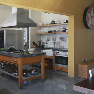 Urban eat-in kitchen photo in Seattle with stainless steel appliances, a farmhouse sink, open cabinets, medium tone wood cabinets, concrete countertops, white backsplash and subway tile backsplash