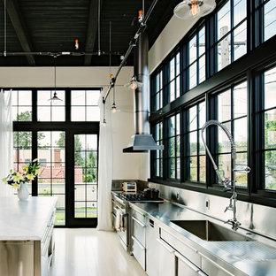 Идея дизайна: прямая кухня в стиле лофт с монолитной раковиной, плоскими фасадами, кухней из нержавеющей стали, столешницей из нержавеющей стали, фартуком цвета металлик, фартуком из металлической плитки, техникой из нержавеющей стали и обеденным столом