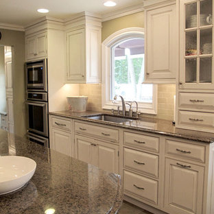 Large traditional single-wall separate kitchen in New York with an undermount sink, raised-panel cabinets, white cabinets, granite benchtops, beige splashback, travertine splashback, stainless steel appliances, slate floors, with island and beige floor.