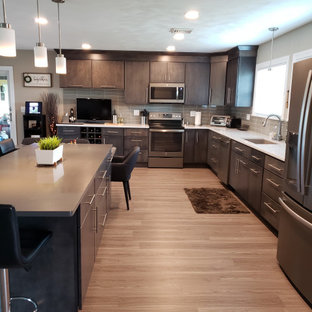 Design ideas for a large contemporary l-shaped eat-in kitchen in Chicago with an undermount sink, flat-panel cabinets, grey cabinets, quartz benchtops, grey splashback, glass tile splashback, stainless steel appliances, vinyl floors, multiple islands, grey floor and white benchtop.