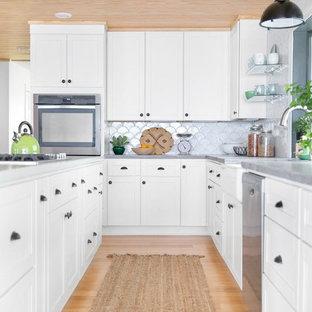 Diseño de cocina en L, clásica renovada, con fregadero sobremueble, armarios estilo shaker, salpicadero blanco, salpicadero de azulejos de cerámica, electrodomésticos de acero inoxidable, suelo de bambú, puertas de armario blancas, una isla y encimera de cemento