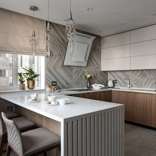This is an example of a mid-sized contemporary u-shaped kitchen in Delhi with an integrated sink, flat-panel cabinets, medium wood cabinets, grey splashback, black appliances, a peninsula, grey floor and white benchtop.