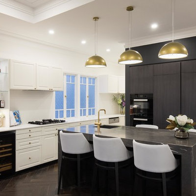 Example of a transitional l-shaped dark wood floor eat-in kitchen design in Brisbane with an undermount sink, flat-panel cabinets, black cabinets, black appliances and an island