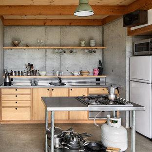 ウェリントンの小さいインダストリアルスタイルのおしゃれなキッチン (フラットパネル扉のキャビネット、淡色木目調キャビネット、ステンレスカウンター、白い調理設備) の写真