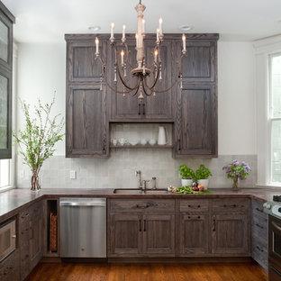 サンフランシスコの中サイズのヴィクトリアン調のおしゃれなコの字型キッチン (ダブルシンク、インセット扉のキャビネット、濃色木目調キャビネット、人工大理石カウンター、グレーのキッチンパネル、セラミックタイルのキッチンパネル、シルバーの調理設備の、無垢フローリング、茶色い床) の写真