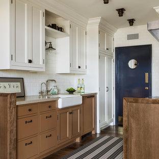 Foto de cocina de galera, clásica, pequeña, sin isla, con fregadero sobremueble, armarios con paneles empotrados, puertas de armario marrones, salpicadero blanco, salpicadero de azulejos tipo metro y suelo de madera oscura