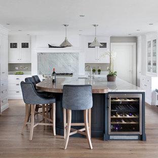 Große Klassische Küche in U-Form mit Schrankfronten im Shaker-Stil, weißen Schränken, Marmor-Arbeitsplatte, Küchenrückwand in Grau, Rückwand aus Marmor, weißen Elektrogeräten, braunem Holzboden, Kücheninsel, braunem Boden, grauer Arbeitsplatte und Unterbauwaschbecken in Dublin